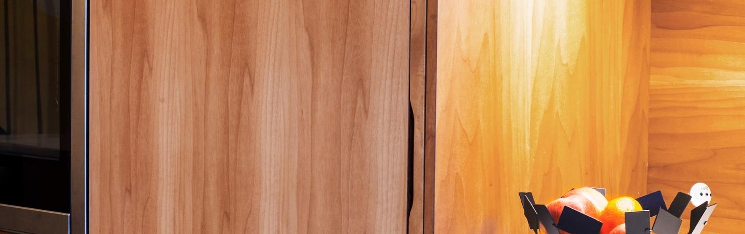 """Centrul acestei bucătării este insula """"Le Baou"""", un cuvânt provincial ce face referire la """"piatră"""". Insula de bucătărie din HI-Macs Crystal Beige pare să fi fost sculptată într-o manieră monolitică astfel încât să fie în contrast cu peretele din lemn de pe fundal. Peretele găzduiește în mod discret cuptorul, mașina de spălat vase și chiuveta, în timp ce restul aparatelor[…] Mai mult…"""